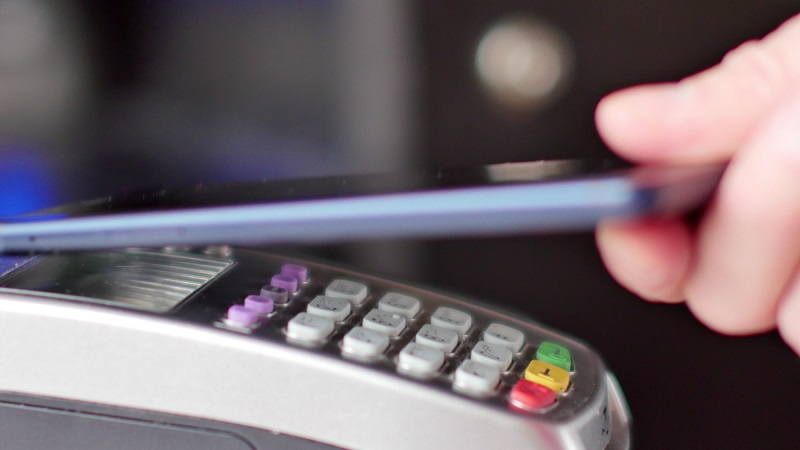 Customer paying with NFC technology by mobile phone on terminal.