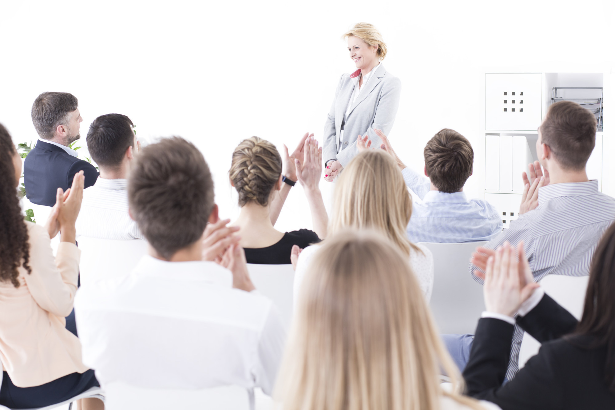 Group of office workers clapping hands at their middle-aged colleague during a staff meeting