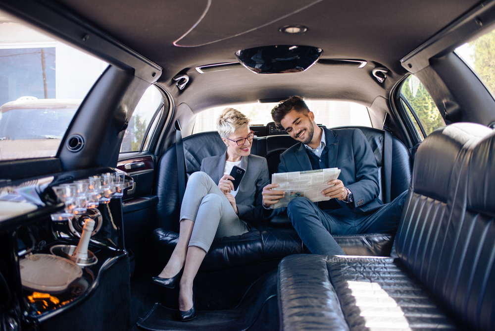 Partners,In,Limo,Looking,At,Newspaper,,Getting,Informed
